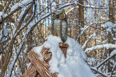 Park sculpture of an owl in a winter forest stock image