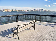 Park seat overlooking NYC midtown cityscape. Empty park seat overlooking NYC midtown cityscape, on a bright sunny day Stock Image