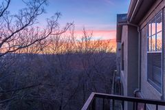 Park side apartment complex balcony during winter sunrise with dramatic clouds. Aerial view from balcony of typical park side apartment complex during winter royalty free stock photography