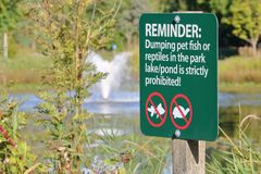 Park Sign Restrictions. A park sign warns that a person can not dispose of fish or reptiles in the pond Royalty Free Stock Images