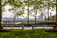 Park sitting area landscape with urban skyline background. Metropolis skyline behind a park area. Trees and park benches framing a spring morning. Skyscrapers Royalty Free Stock Photography