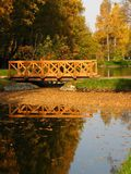 Park Sokolniki Moscow. Autumn landscape with lake, island with two golden birches and bridge, reflection of trees in water. Recorded in park Sokolniki in Moscow Stock Photos