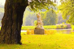 Park. Statue,autumn trees and the sun Stock Image