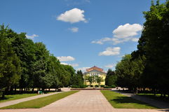In the Park. Park, street, trees,blue sky, white clouds,green bench,the Avenue,grass,yellow house in the center of the frame Stock Photo