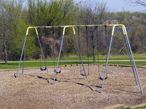 Park Swingset. Swingset in the park with trees and lake in the background Stock Photography