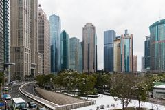 Park with trees and road covered with snow surrounded by skyscrapers in the Pudong area. Shanghai, China Stock Photography