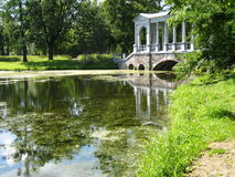 Park in Tsarskoye selo. Landscape with colonnade bridge on the lake in park belongs to palace of queen Ekaterina Second Great in Tsarskoye selo, near St Royalty Free Stock Photo