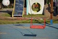 In the park. Two red swings in the park and shadow Royalty Free Stock Photos