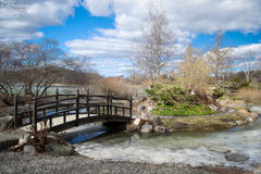 Park walk. A beautiful park walk in a japanese garden by the lake. Small wooden bridge crossing a partially frozen river Stock Photography