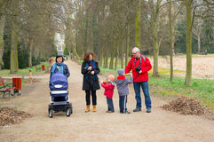 Park walk. Group of parents walking with their children on a footpath at the arboterum park Stock Image