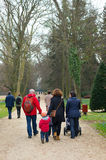 Park walk. Group of parents walking with their children on a footpath at the arboterum park Royalty Free Stock Images