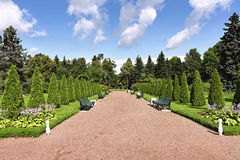 Park walkway with benches for rest and flower beds on either sid Royalty Free Stock Photography