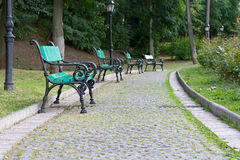 Park walkway of paving stones and benches. Royalty Free Stock Photo
