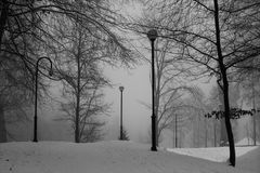 Park in winter time. Path in the snowy park. Trees covered with royalty free stock images