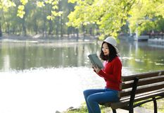 Park woman reading book on bench smiling happy at camera. Pretty young multicultural woman enjoying spring in park along river. Asian chinese Woman reading a Stock Photos