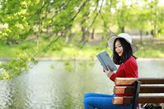 Park woman reading book on bench smiling happy at camera. Pretty young multicultural woman enjoying spring in park along river. Asian chinese Woman reading a Royalty Free Stock Image