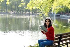 Park woman reading book on bench smiling happy at camera. Pretty young multicultural woman enjoying spring in park along river stock photos
