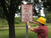 Park worker installing animal sign Stock Images
