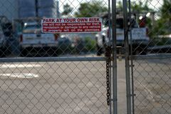 Park At Your Own Risk. A gate with a sign reading Park at your own risk, and why. The gate is locked; there are a couple trucks parked in the background Royalty Free Stock Image