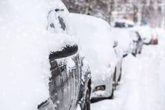 Parkautos nach Schneefällen Automobile bedeckt mit Schnee Portrait eines tragenden weißen Kleides des schönen Mädchens stockfoto