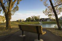 Parkbank langs mooie sleep in de herfst Royalty-vrije Stock Foto's