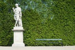 Parkbank met beeldhouwwerk stock foto