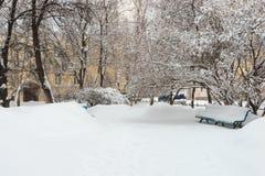 Parkbank und -bäume bedeckt durch starke Schneefälle Lizenzfreie Stockfotografie