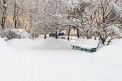 Parkbank und -bäume bedeckt durch starke Schneefälle Lizenzfreies Stockbild