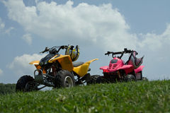 Parked ATVs. Two ATVs parked on a hill with a blue sky Royalty Free Stock Photography