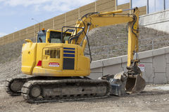 Parked Backhoe At Construction Site. A yellow backhoe parked at a construction site Stock Photo