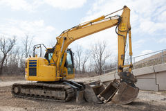 Parked Backhoe At Construction Site. A yellow backhoe parked at a construction site Stock Images