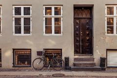 Parked bicycle with basket near grey building with closed doors on street. In copenhagen, denmark royalty free stock images