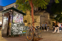 Parked bicycle, graffiti and people passing by Panagia Kapnikare Royalty Free Stock Photography