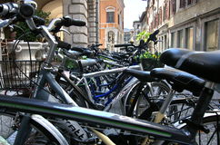 Parked bicycles. A line of bicycles for men and women are narrowly parked in a street of the centre of Udine in Italy Stock Images