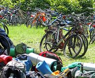 Parked bicycles and many backpacks on the lawn during a stop in Royalty Free Stock Photo