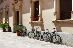 Parked bicycles near a building in Alcudia. Parked bicycles near a beautiful building in Alcudia, Spain Royalty Free Stock Images
