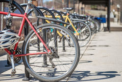 Parked bicycles. Bicycles showing rear wheel  locked and parked at the bicycle rack in a row during day time Royalty Free Stock Image