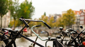 Parked bikes alongside a canal in Amsterdam. Parked bikes/bycycles alongside the canal in Amsterdam Stock Photography