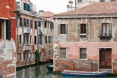 Parked boats on a narrow Venetian canal with turn. Royalty Free Stock Image