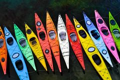 Parked Canoes. A set of nicely arranged colorful canoes with different sizes Stock Image