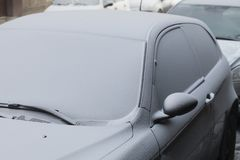 Parked car covered with the first snow in winter Royalty Free Stock Photography