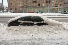 Car covered with snow on the side of the road royalty free stock images