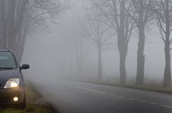 Parked car by road on fog Stock Photos