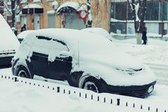 Parked car stands along the road all in the snow Stock Image