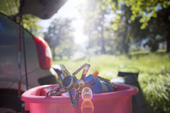 Parked car in woodland clearing, focus on camping stove in pink container (backlit) stock image