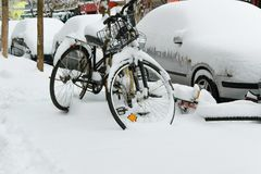 Parked cars and bicycles covered by the snow. Space for text Royalty Free Stock Photos