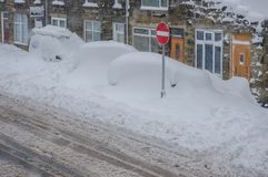 Parked cars buried in snow during a winter blizzard. Cars buried under snow. Parked cars in front of reential houses in a village are covered in snow during a Stock Photography