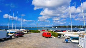 Parked cars and moored boats at a marina on a sunny summer day beneath a beautiful blue sky royalty free stock images