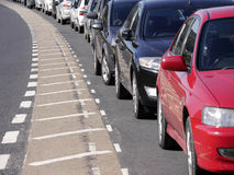 Parked cars on road. A row of parked cars curving around bend in road Stock Images