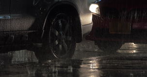 Parked cars under the rain at night. Two cars parked at the roadside under the heavy rain in night city. Logo washed out stock footage